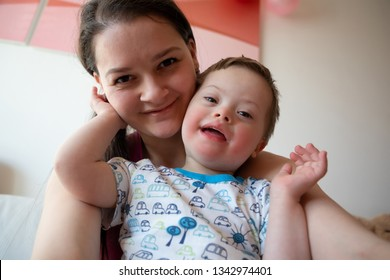 Selfie of cute small boy with Down syndrome with his young mother