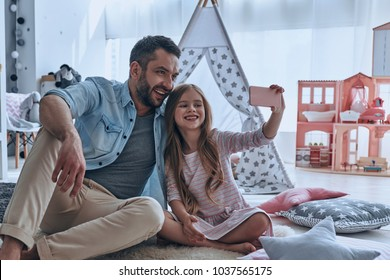 Selfie with dad. Young father and his little daughter taking selfie while sitting on the floor in bedroom with the tent in the background
