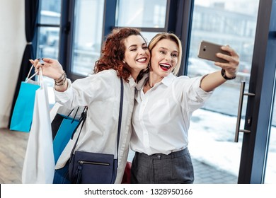 Selfie with daughter. Blonde-haired appealing mature mom making selfie with her lovely beautiful daughter