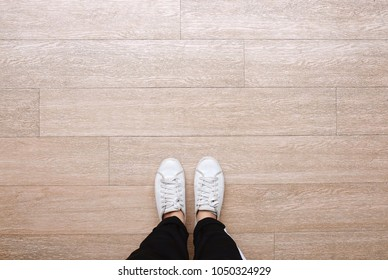 Selfie of feet in fashion sneakers on wooden floor background, top view with copy space