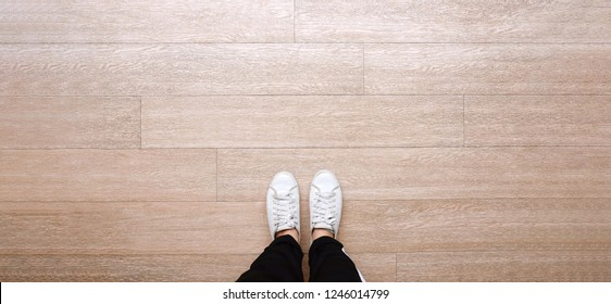 Selfie of feet in fashion sneakers on wooden floor background, top view with copy space, banner style for text