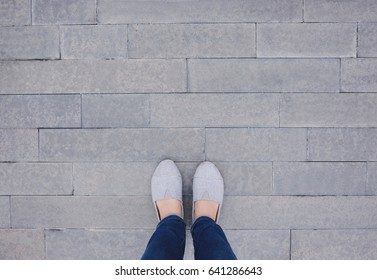 Selfie of feet and shoes on pavement background with copy space, top view