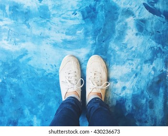 Selfie of feet in sneaker shoes on blue concrete floor background, top view