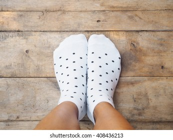 Selfie feet wearing white polka dot socks on wooden floor background