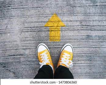 Selfie feet wearing yellow sneakers in front of arrow on concrete road. Start moving forward concept