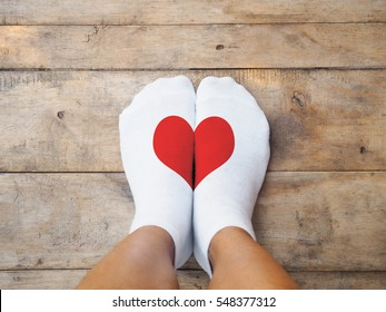 Selfie feet wearing yellow socks with red heart shape on wooden floor background. Love self concept.