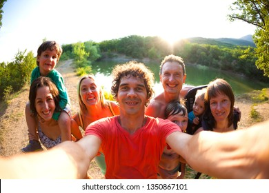 Selfie of friends on nature. Friends are resting near the lake. Great fun company. Big family gathered together on vacation. Children and parents on a picnic in the summer forest.