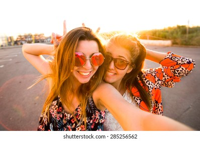 Selfie fun girls taking picture at cool sunset.Summer holidays, girls at smartphone camera taking self-portrait on their travel vacations.Best friends girls make picture at sunset,camera selfie pic