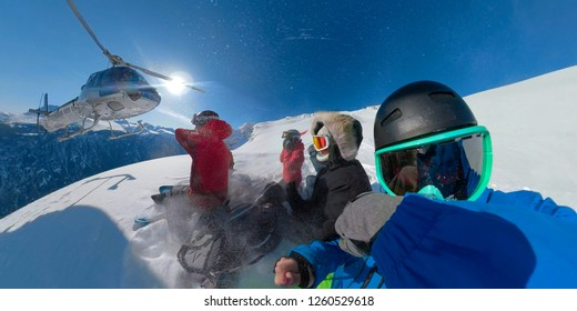 SELFIE: Group of young extreme snowboarders waiting for the helicopter to pick them up in the spectacular sunny mountains in British Columbia. Helicopter arrives to take the tourists heliskiing.