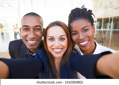 Selfie of happy beautiful intercultural business friends in office. Smiling pretty woman taking group photo with black colleagues. Staff relationship concept