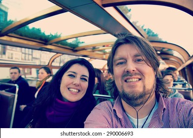 Selfie of happy couple on holidays in Amsterdam with filters applied for hipster look