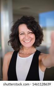 Selfie der glücklichen freudigen, hässlichen Frau in der Gelegenheitsarbeit. Aufregte Dame mittleren Alters, die Smartphone hält und sich selbst fotografiert. Happy-Women-Portrait-Konzept