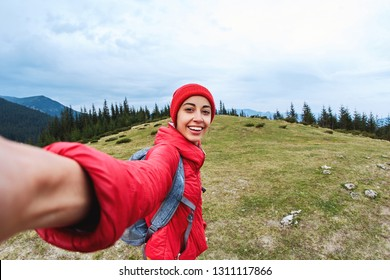 selfie image of a young smiling woman hiker with small backpack standing on a mountain slope. woman hiker taking selfie in the mountains. Follow me, hiking, active and travel lifestyle concept.