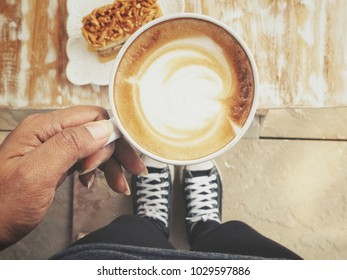 Selfie of latte art coffee with cake and sneakers
