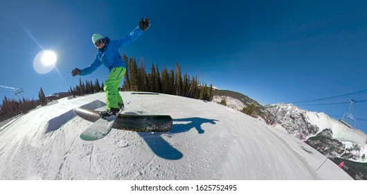 SELFIE, LENS FLARE: Awesome action shot of a snowboarder sliding along a railing placed in a snow park on Copper Mountain. Tourist on active vacation in Colorado goes snowboarding around a fun park.
