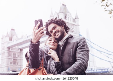 Selfie - Loving couple taking pictures with your cell phone in front of Tower Bridge, London