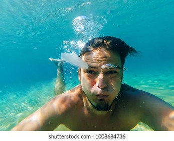 selfie of a man with a funny surprised face under water and jellyfish