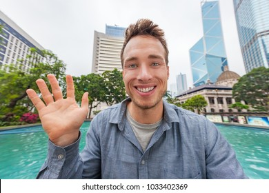 Selfie man waving hello talking to camera chatting online on video conference or recording videoblog vlog vlogging for social media app. Young people trave lifestyle in Hong Kong, China, Asia.