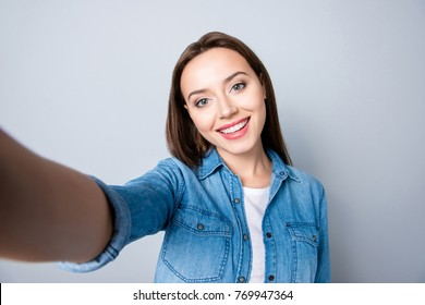 Selfie mania. Close up of confident brunette girl  with beaming smile in denim oufit taking a self-portrait  on her mobilephone and  standing over grey background