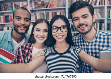 Selfie mania! Four international students with beaming smiles are posing for selfie shot, asian attractive lady is taking, in school library building. Gathered, cheerful, smart and successful youth