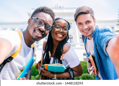 Selfie mania. Three international students with beaming smiles are posing for selfie shot, caucasian hansome guy is making, outside school building. Gathered, cheerful, smart successful youth concept.