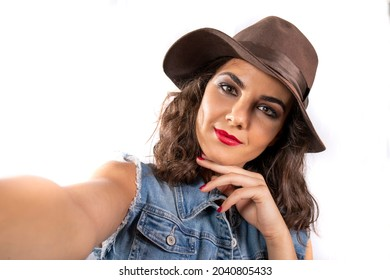 Selfie mania! Young attractive woman with a brown hat and a jeans outfit taking a selfie. Intense and dreaming gaze underlined by the eyes' makeup and the left hand under the chin.