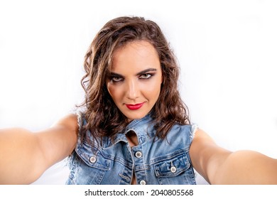 Selfie mania. Young attractive woman with brown hair and a jeans outfit taking a selfie. Intense gaze underlined by the eyes' makeup.