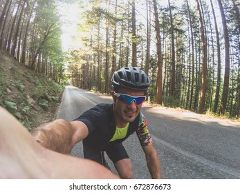 Selfie on bicycle. Young adult athlete takes a self portrait with a wearable camera while training on a racing bicycle on summer.