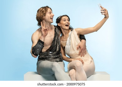 Selfie on mobile phone. Young couple of ballet dancers in ancient Rome costums at blue studio as modern man, woman. Historical character, creative, classical art, humor and comparison of eras concept. - Shutterstock ID 2000975075