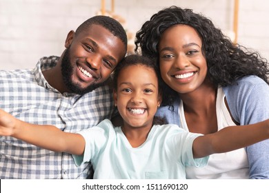 Selfie with parents. Cute little girl taking photo with her mom and dad, spending time together at home