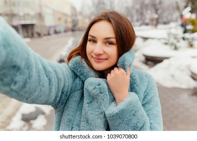 Selfie photo of smiling attractive girl with paper bags after shopping. Laughing pretty woman wearing fur coat in winter time make selfie portrait.