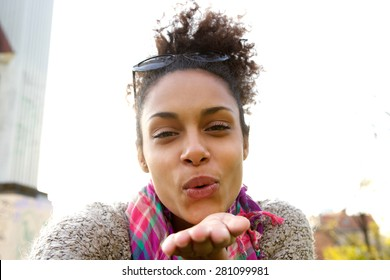 Selfie portrait of an attractive young woman blowing a kiss
