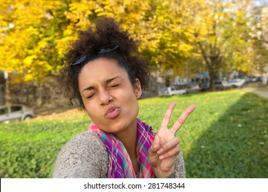 Selfie portrait of a cute girl making face with peace sign