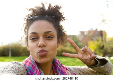 Selfie portrait of a cute girl making fun face with peace sign