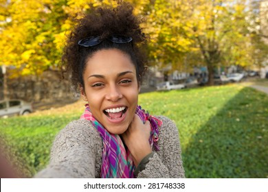 Selfie portrait of a happy young woman outside in the park