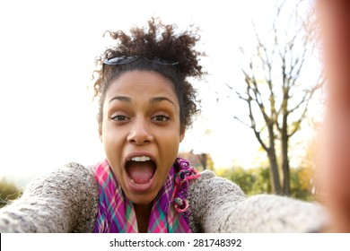 Selfie portrait of a happy young woman shouting