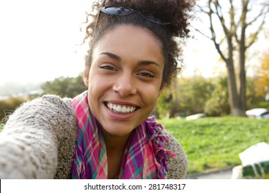 Selfie portrait of a smiling young woman happy to be outdoors