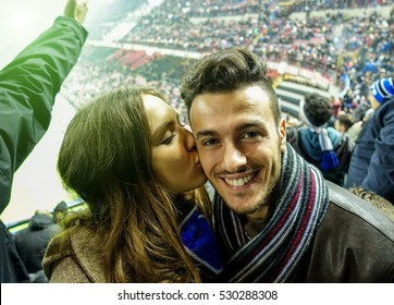 Selfie portrait of young couple watching sport soccer match in football italian stadium - Young people having fun together - Love for sport concept - Focus on man - Warm filter with stark arena lights