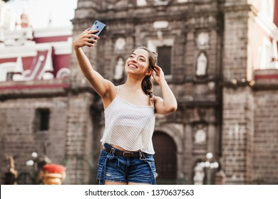Selfie Portrait of a young latin woman in the street with a smartphone in Mexico