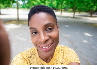 Selfie of positive black woman in park. Attractive young woman talking self-portrait outdoors. Stroll concept