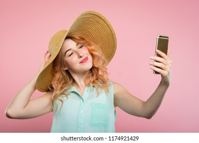 selfie and self adoration. young stylish woman in a big sunhat taking a photo of herself using mobile phone. modern lifestyle and trends.