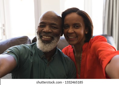 Selfie of a senior couple having fun on the sofa in living room at home
