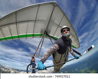 Selfie shot of brave extreme hang glider pilot soaring the thermal updrafts above mountains taken with action camera