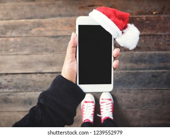 Selfie of smart phone with christmas hat and sneakers