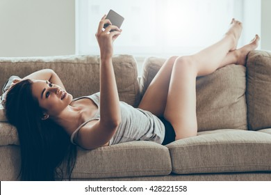 Selfie time. Beautiful young woman in panties and tank top making selfie by smart phone while lying on couch at home