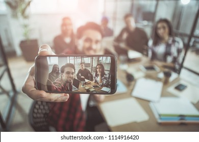 Selfie time. Close up of screen of modern smartphone in hand of cheerful guy. He is sitting at table in office with his members of team and taking picture of them. Focus on gadget with photo