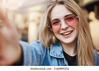 Selfie time. Close-up of charming confident and stylish caucasian blond woman in trendy pink sunglasses and denim, pulling hand towards camera to take photo, smiling joyfully, updating profile shot