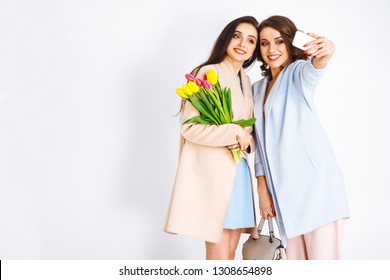 Selfie time! Fashion photo of two beautiful young women with tulips in the hand .they  dressed in a beautiful coat, and T-shirt with stripes.Spring concept.March 8. beautiful girls in stylish clothes