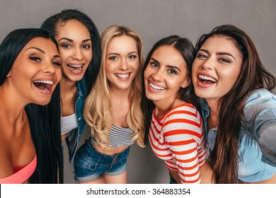 Selfie time! Five beautiful women bonding to each other and smiling while making selfie against grey background