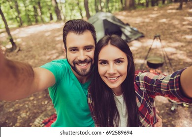 Selfie time! For a memories of vacation together. Cute lovers are making photo in a campsite, hugging, smiling, so happy